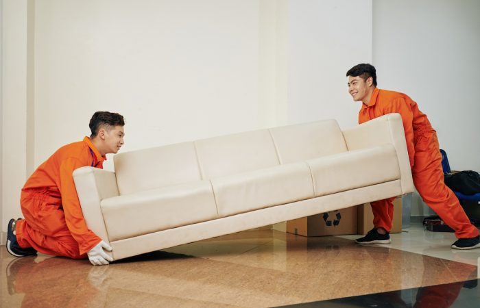 Smiling moving service company workers in uniform carrying heavy couch